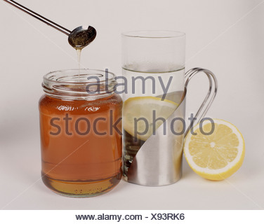 Silver mug steamed glass containing hot water and a lemon slice silver spoon hanging over opened jar of honey half a lemon - Stock Photo