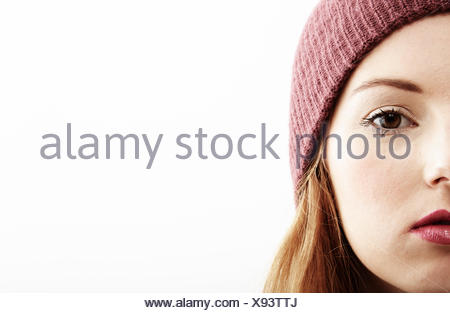 Half face close up studio portrait of young woman - Stock Photo