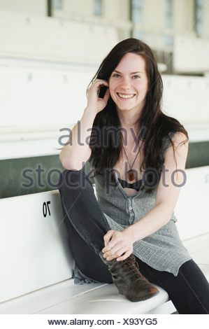 Smiling woman sitting on bench - Stock Photo