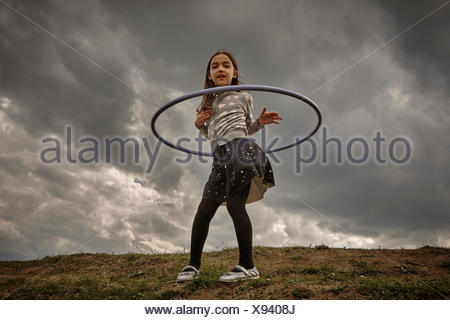 Girl playing with hoola hoop - Stock Photo