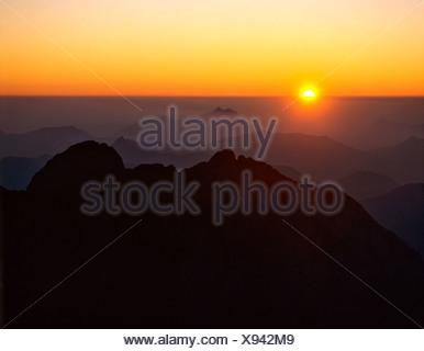 Sunrise, view from the Birkkarspitze, backlight, in front Falkengruppe, Karwendel, Tyrol, Austria - Stock Photo