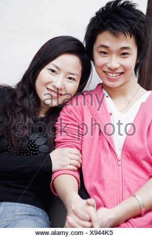 Portrait of a teenage boy smiling with a young woman - Stock Photo