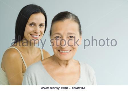 Woman standing behind senior woman, both smiling at camera, portrait - Stock Photo