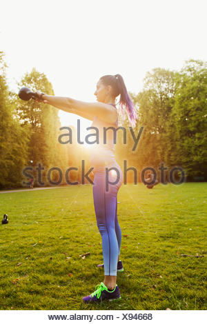 Young woman exercising with kettlebell standing on grassy field against clear sky - Stock Photo