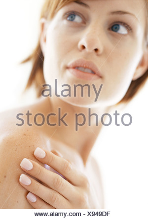 Woman with hand on shoulder, close-up - Stock Photo
