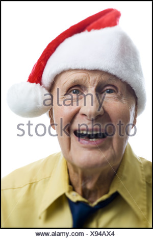 Portrait of a senior man wearing a Santa hat and laughing - Stock Photo