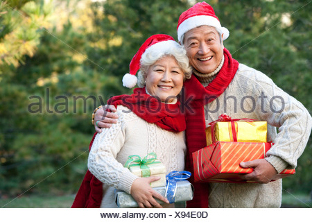 Senior Couple in Santa Hats Holding Christmas Gifts - Stock Photo