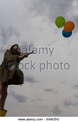 Female watching as bunch of balloons float away up into cloudy sky - Stock Photo