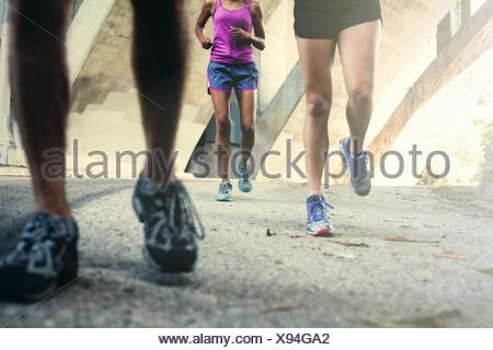 Joggers running on bridge - Stock Photo