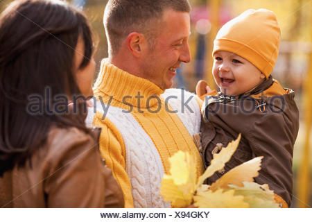 Cheerful parents looking at son in park during autumn - Stock Photo