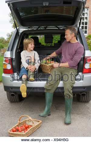 Father and son 8 10 sitting beside basket of fresh vegetables in car boot smiling - Stock Photo
