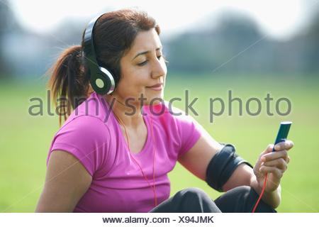 Mature woman taking exercise break in park selecting music from MP3 player - Stock Photo