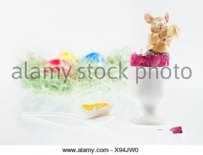 An Easter bunny figurine in a boiled egg with the top cut off, with an Easter nest of colourful eggs in the background - Stock Photo