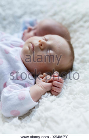 Portrait of sleeping newborn baby girl lying besides her twin brother - Stock Photo