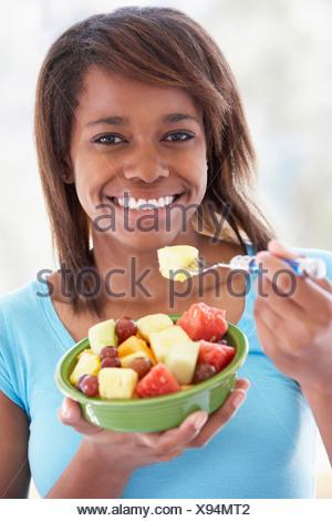 Teenage Girl Eating Fresh Fruit Salad - Stock Photo