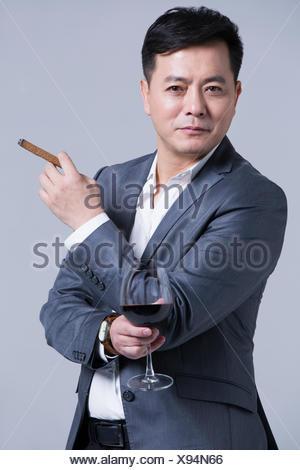 Mature businessman enjoying cigar and wine - Stock Photo