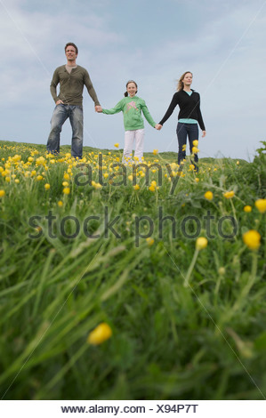 Parents and child stand on hillside - Stock Photo