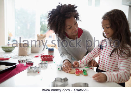 Mother and daughter decorating Christmas gingerbread cookies in kitchen - Stock Photo