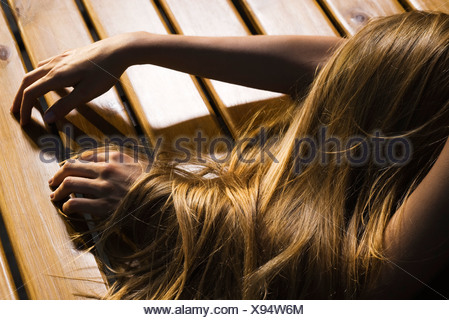 Woman lying face down on floor, long hair covering arm, cropped - Stock Photo
