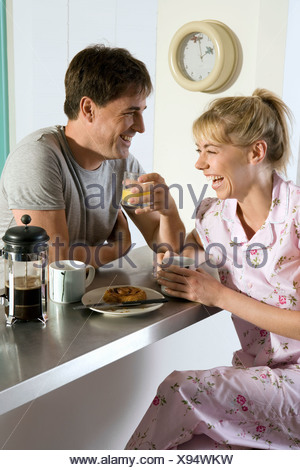 Couple in pyjamas sitting at breakfast bar in kitchen holding mug and glass laughing side view - Stock Photo