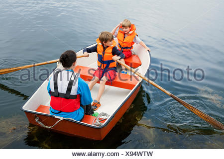 Sweden, Uppland, Runmaro, Barrskar, Woman with two boys in rowboat - Stock Photo