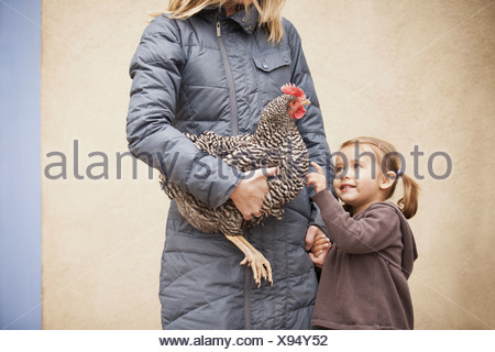 A woman in a grey coat holding chicken with a red coxcomb under one arm. A young girl beside her holding her other hand - Stock Photo