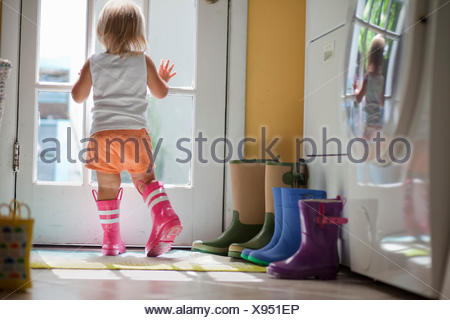 Female toddler wearing rubber boots looking out of back door window - Stock Photo