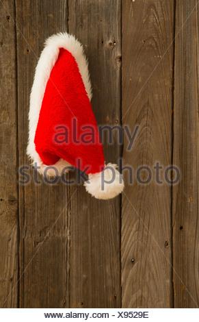 Santa hat hanging on wooden door - Stock Photo