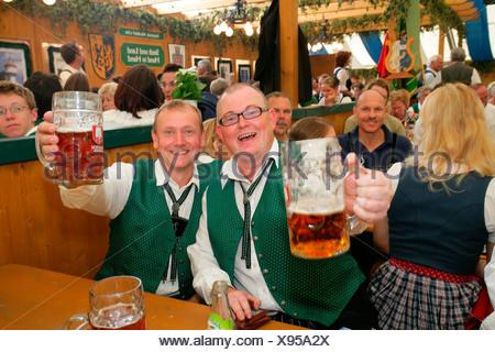 Men dressed in national costume holding up their beer mugs at a folk festival in Muehldorf am Inn, Upper Bavaria, Bavaria, Germ - Stock Photo