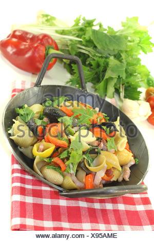 Nudelpfanne mit Paprika, Schinkenspeck und Tomaten vor hellem Hintergrund - Stock Photo