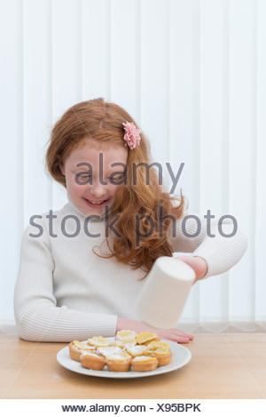 Little girl making marzipan covered mine pies. - Stock Photo