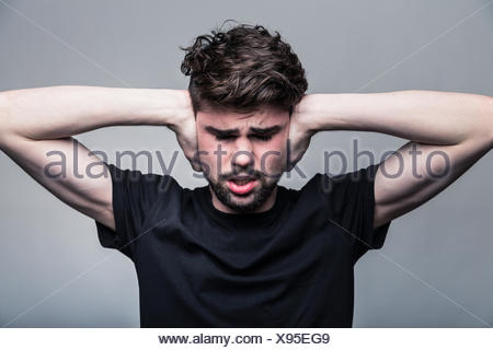 I need silence. Frustrated young man in shirt - Stock Photo
