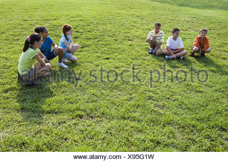 Three boys sitting opposite three girls on grass at a park - Stock Photo