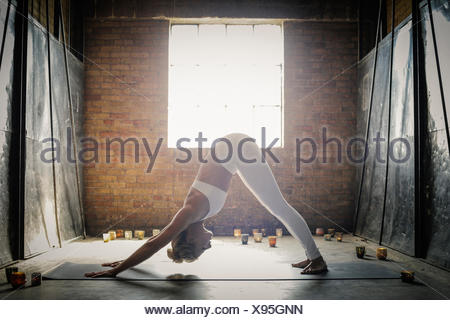 A blonde woman, in a white crop top and leggings, bending down on the floor surrounded by candles, in a yoga position. - Stock Photo
