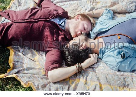 Overhead view of male couple kissing on picnic blanket - Stock Photo