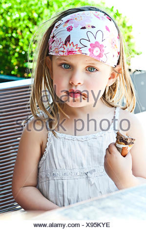 Girl eating ice cream with chocolate mess around mouth - Stock Photo