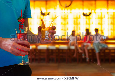Young man carrying cocktails in bar - Stock Photo