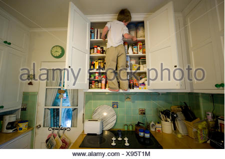 A young boy climbs the cabinets in a kitchen looking for food. - Stock Photo