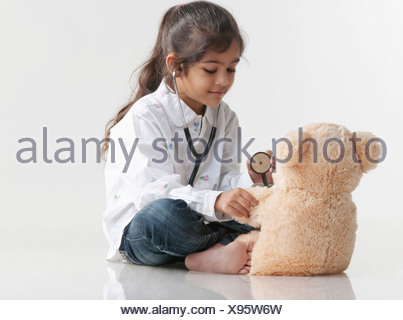 Girl playing doctor with teddy bear - Stock Photo