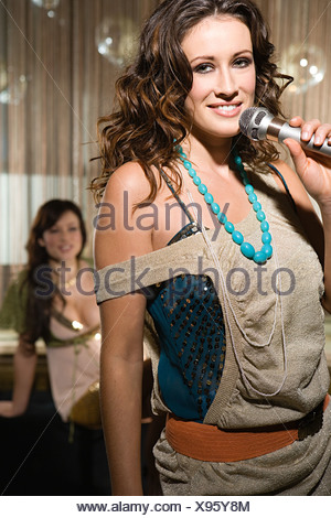 Young woman doing karaoke - Stock Photo