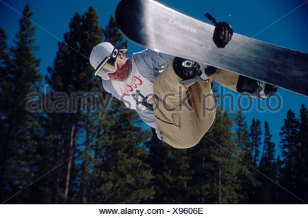 Leaping snowboarder in midair competing in a half pipe contest at Copper Mountain Ski Resort CO - Stock Photo