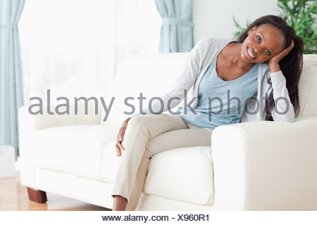Woman enjoys sitting on the couch - Stock Photo