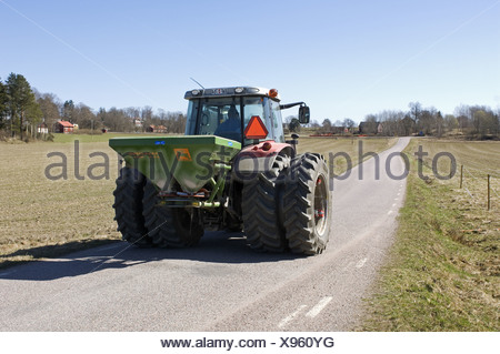 Tractor with Amazone ZA-F fertiliser spreader, driving along rural road, Sweden, spring - Stock Photo