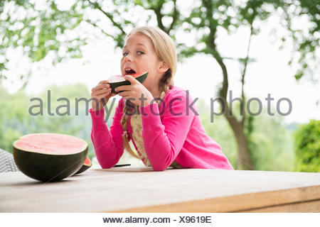 Girl at patio table eating watermelon slice - Stock Photo