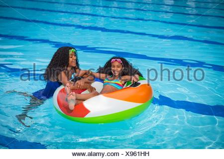 Girls in swimming pool playing with inflatable ring, smiling - Stock Photo