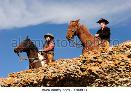 Cowboy and cowgirl on horses looking into the distance, Saskatchewan, Canada, North America - Stock Photo
