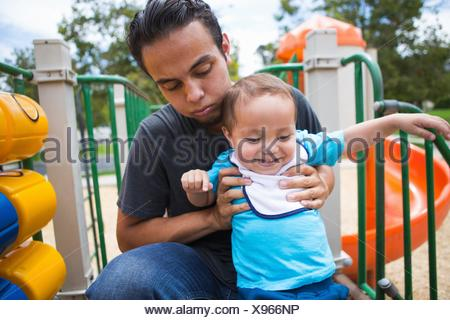 Young man guiding toddler brother on playground slide - Stock Photo