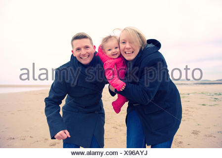 Family portrait of smiling mother, father, and daughter (6-11 months) embracing on beach - Stock Photo
