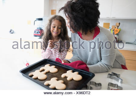 Mother and daughters baking Christmas gingerbread cookies in kitchen - Stock Photo