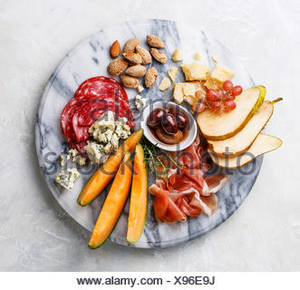 Meat and cheese plate antipasti snack with Prosciutto ham, Salami, Parmesan, Blue cheese, Cantaloupe melon and Olives on marble board